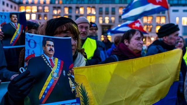 Purtret da protestas a Venezuela. Ina dunna tegna enta maun in purtret da Maduro.