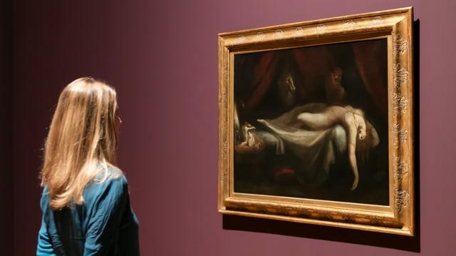 Eine Frau begutachtet ein Kunstwerk im Museum