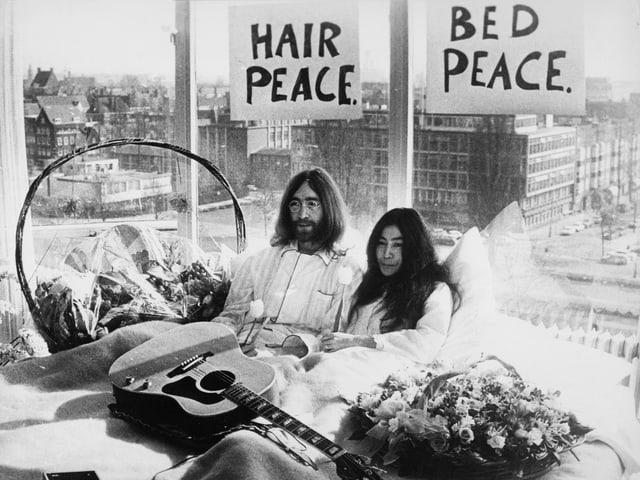 Lennon und Ono 1969 in einem Bett. Im Hintergrund Friedens Parolen.