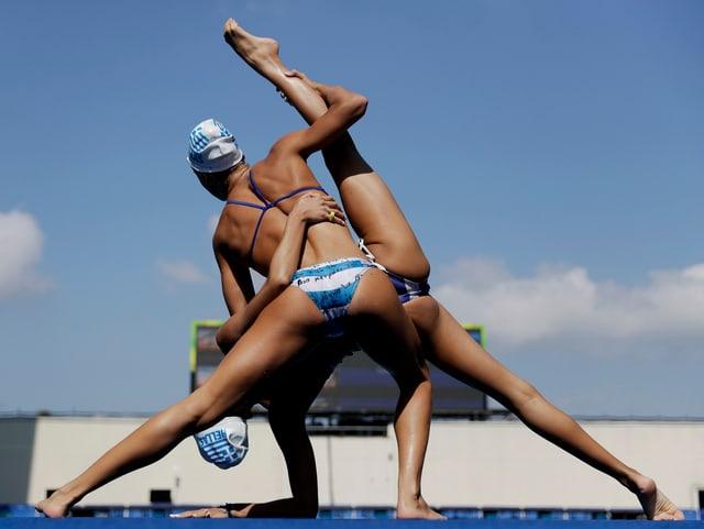 Schwimmerinen bei gymnastischer Figur an Land.