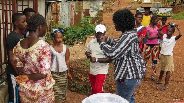 Blindenunterschrift: Eine Frau zeigt einer Gruppe von Männern und Frauen, wie sie ihre Hände waschen sollen. Im Hintergrund Wellblechhütten.