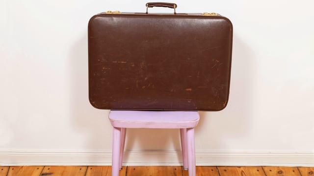 Ein brauner Koffer steht auf einem rosafarbenen Hocker.