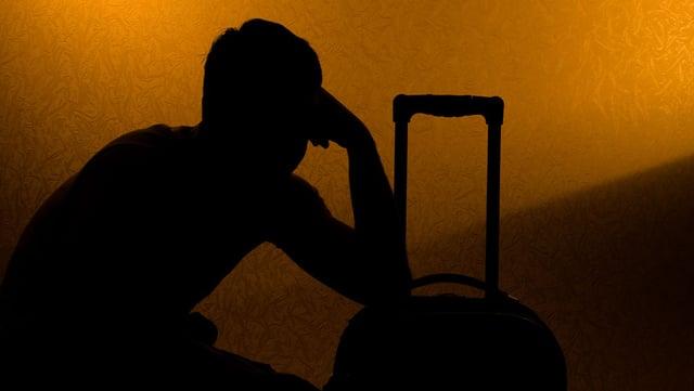 Schattenbild: Ein Mann stützt sich auf einem Koffer ab.