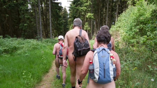 Nackte Personen wandern im Wald