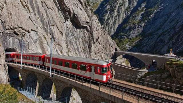 Zug fährt aus dem Tunnel bei der Teufelsbrücke in der Schöllenen.