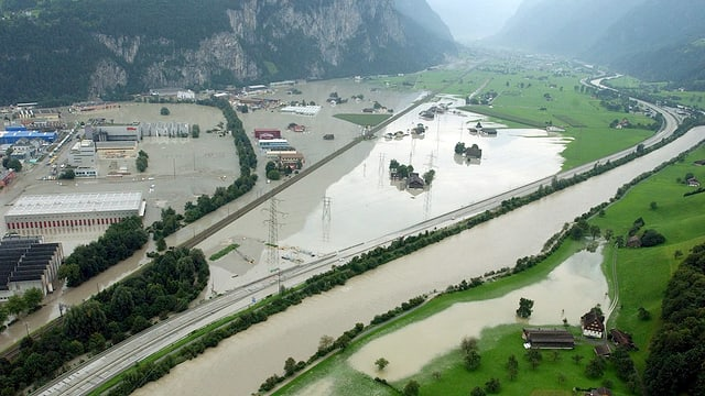 Flugaufnahme von Schattdorf/Uri 2005: die Ebene ist geflutet, Häuser stehen im Wasser, nur die Autbahn und das Bahntrassee sind nicht versunken.