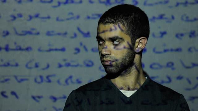 Projektion eines arabischen Textes auf eine Wand und den Körper eines davor stehenden Künstlers.