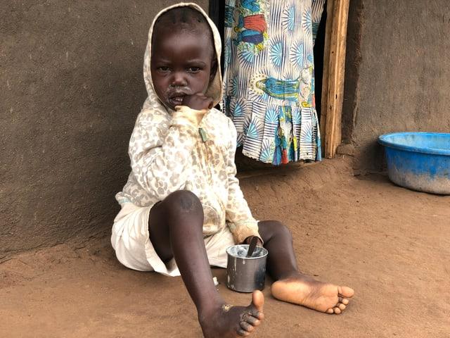 Kind sitzt am Boden und isst.