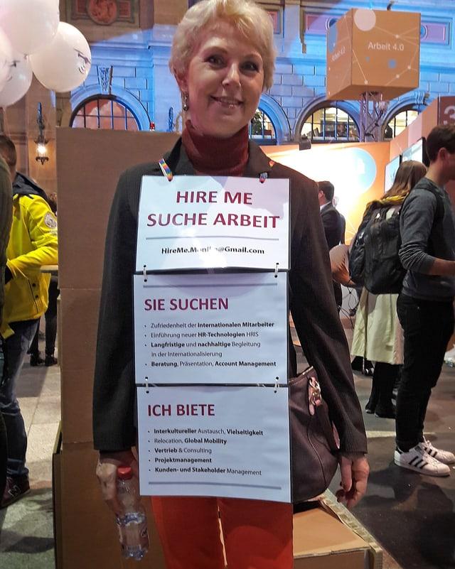 Eine ältere Dame steht am HB Zürich. Sie hat sich mit Schildern behängt, auf denen steht, dass sie eine Stelle sucht.