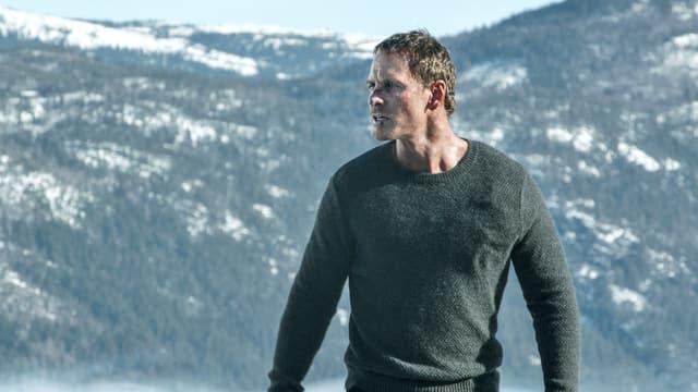 Ein Mann steht wütend vor einer Bergkulisse.