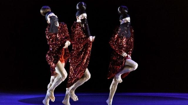 Drei Männer in Glitzerkleid tanzen nebeneinander