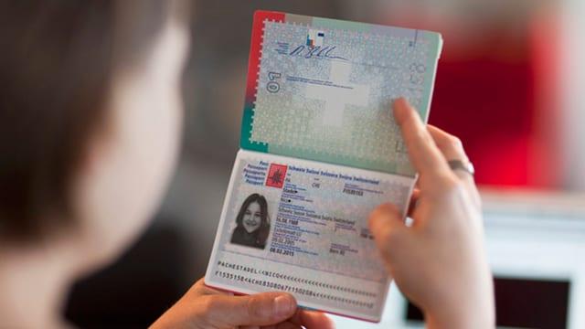 Eine Frau hält einen Schweizer Pass in der Hand