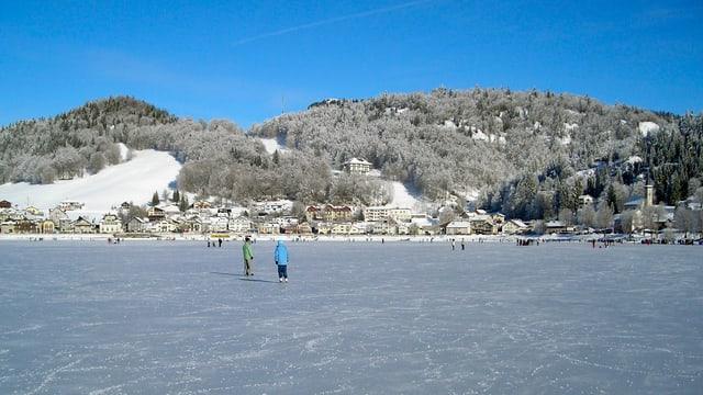 Schlittschuhläufer auf dem zugefrorenen See. Darüber wolkenloser, blauer Himmel.
