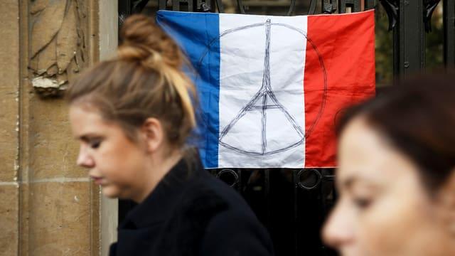 Zwei Frauen gehen an einer «Peace for Paris»-Flagge vorbei.