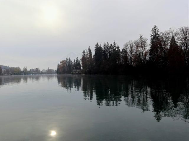 Die Sonne schimmert schwach durch die Wolkenschicht, dennoch spiegelt sich die Sonnenscheibe  auf der  Wasseroberfläche des Thunersees.