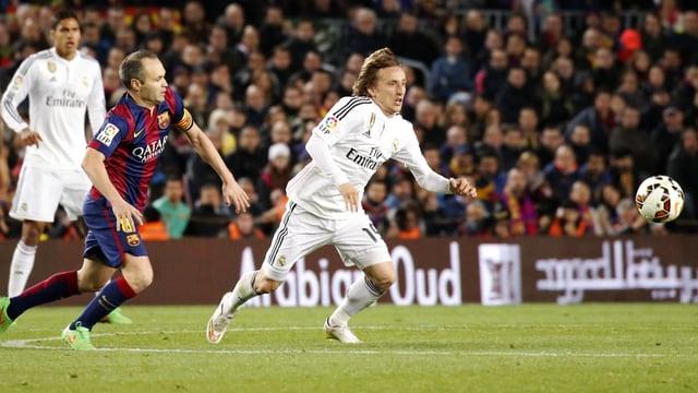 Andres Iniesta und Luca Modric hetzen dem Ball hinterher.