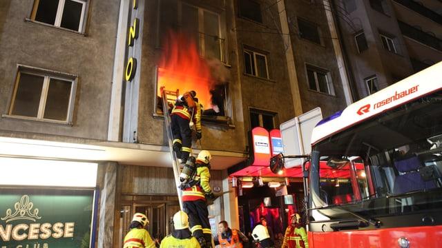 Feuerwehrleute beim Löschen eines Brandes. Feuer aus dem Fenster ist zu sehen.