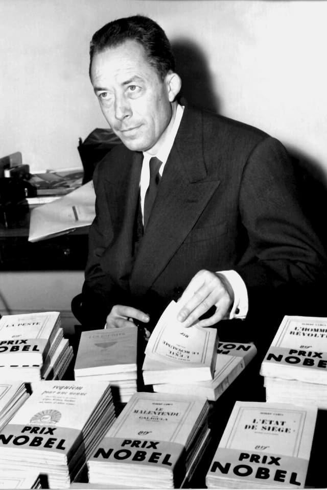 """Camus vor seinen Büchern, die ein """"Prix Nobel""""-Band tragen"""