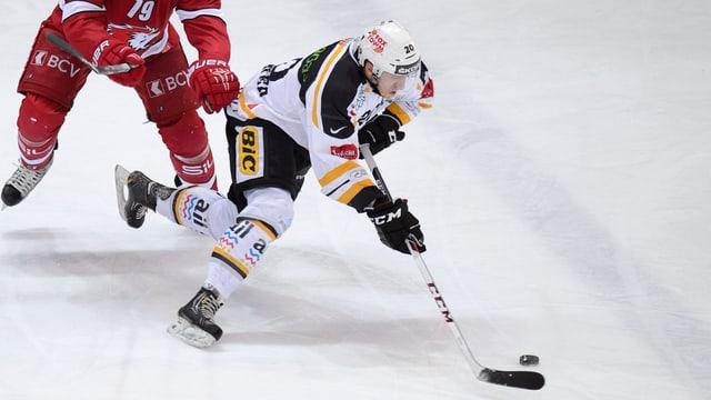Hockeyspieler führt den Puck.