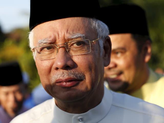 Najib Razak schaut kritisch in die Kamera. Die Sonne strahlt ihm ins Gesicht, er trägt eine Brille und weisse Haare.