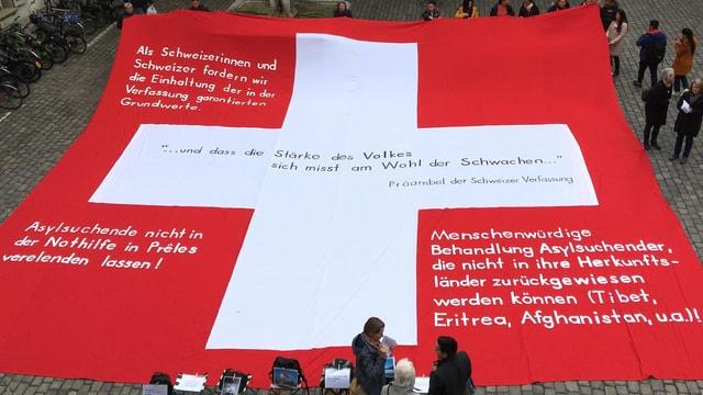 Ein grosses Schweizerkreuz mit Forderungen drauf.