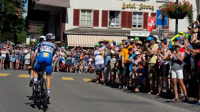 Glieud che persequitescha il Tour de France a l'ur da la via che maina a Berna.