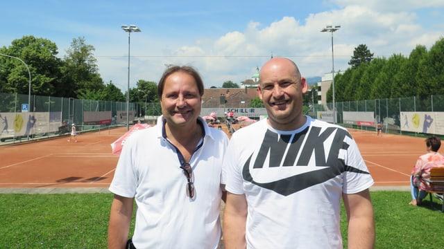 2 Männer stehen von einem Tennisplatz