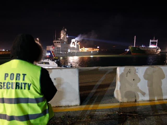 Eine Uniformierte steht an der Pier und beobachtet das Einlaufen der Ezadeen.