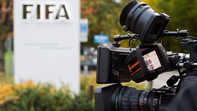 Diverse Kameras und Fotoapperate richten sich auf ein FIFA-Logo.