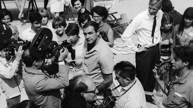 Ein Mann inmitten vieler Menschen und Fotografen