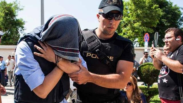 Vor dem Gerichtsgebäude hält der Angeklagte sein Gesicht bedeckt.