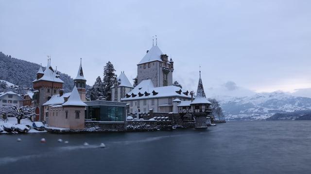 Ein Schloss, verschneit, direkt am Wasser.