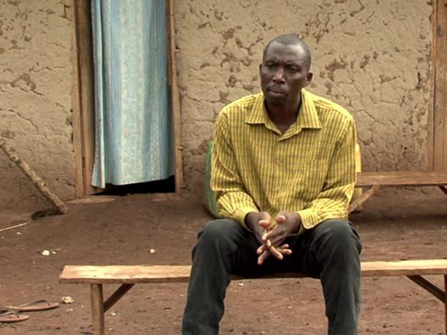 Mann in gelbem Hemd sitzt auf Bank.