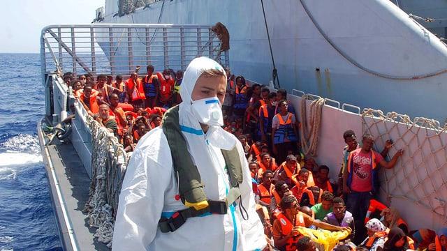 Mann in Schutzanzug mit Flüchtlingen