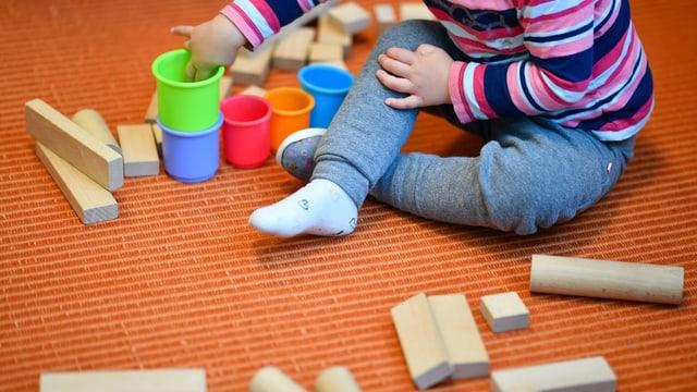 Ein Kind spielt mit Plastikbechern und Holzklötzchen