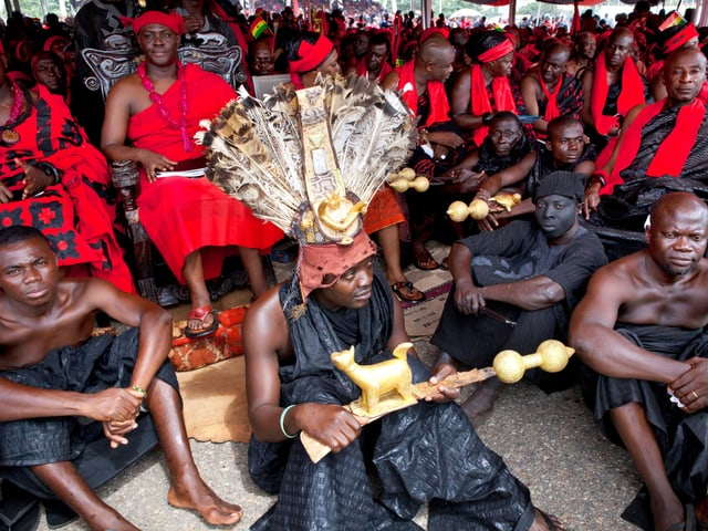 Menschen in rot-schwarzen Kleidern sitzen dicht beieinander