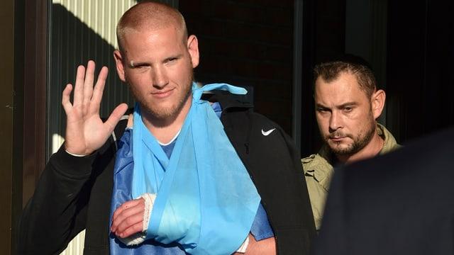 Ein Mann mit Armbinde verlässt das Spital