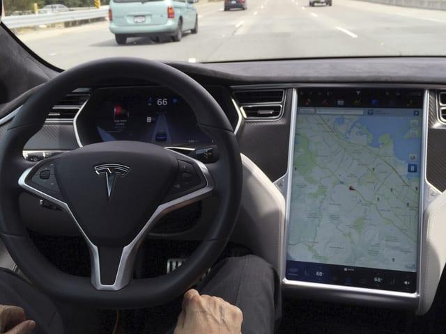 Tesla-Cockpit mit Steuerrad und Navigations-Tablet in der Mittelkonsole. Der Fahrer hat die Hände auf dem Schoss.