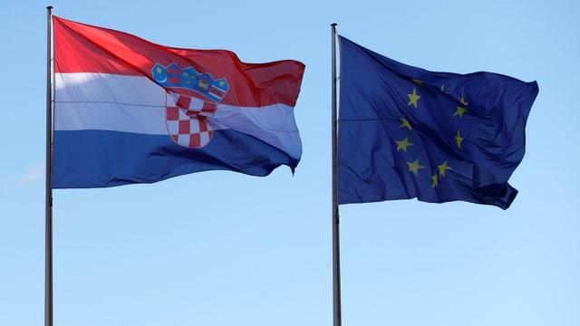 Fahnen Kroatiens und der EU wehen nebeneinander an Fahnenmästen.