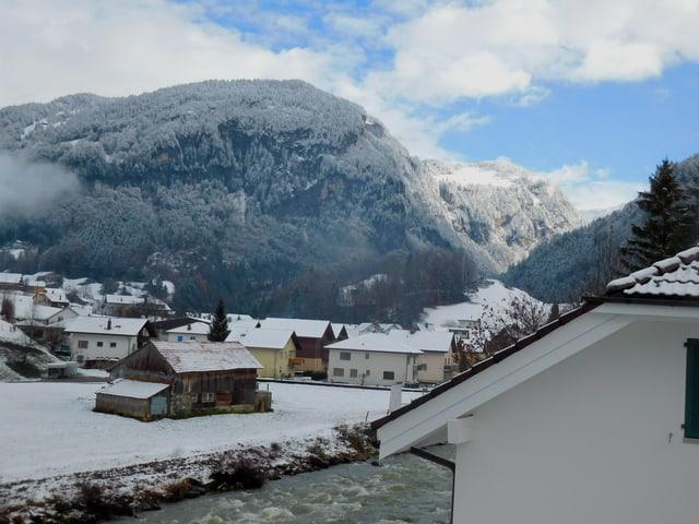 Häuser mit Schnee auf den Dächern, dahinter Berge
