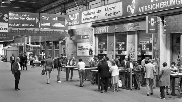 Schwarzweiss-Bild aus dem Jahr 1987. Menschen stehen im Bahnhof Luzern.