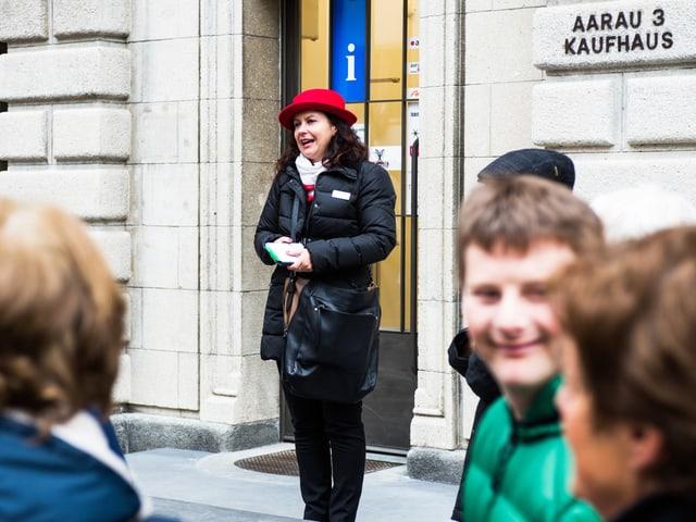 Eine Frau mit rotem Hut steht vor einem Gebäude. Vor ihr sind Menschen.