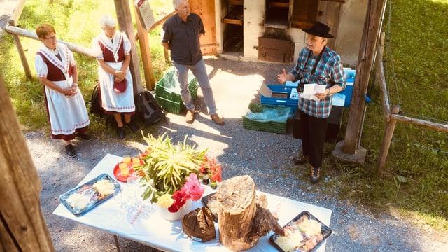 Der Lokalhistoriker Kurt Brigge und weitere Gäste bei der Übergabe des «Holztotz». Dieser steht auf einem Tisch, zusammen mit Blumen und einem Apéro.