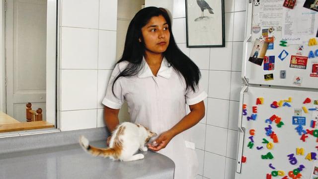 Eine chilenische Hausfrau streichelt in der Küche ihre Katze.