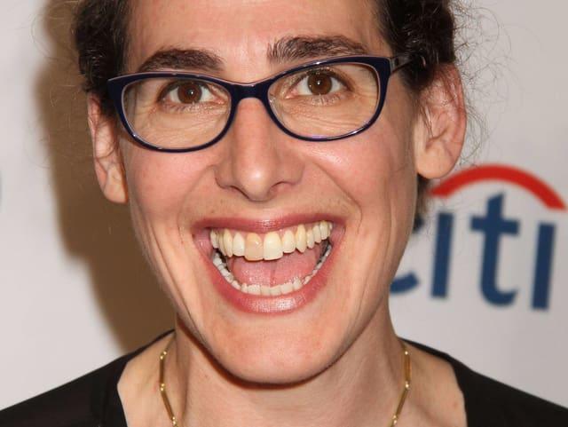 Eine lachende Frau mit braunen Haaren und Brille.