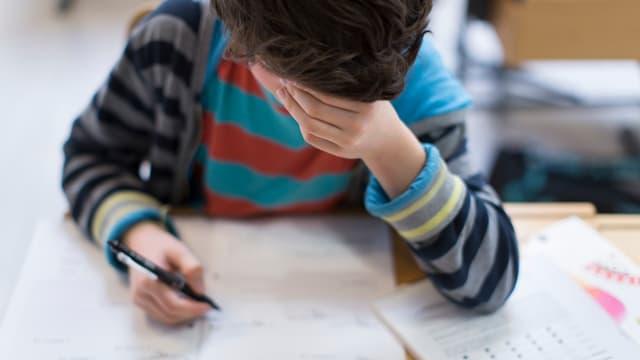 Kind schreibt auf ein Blatt und hat Kopf auf die Hand gestützt