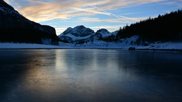 Der gefrorene See, dahinter eine Bergkulisse.