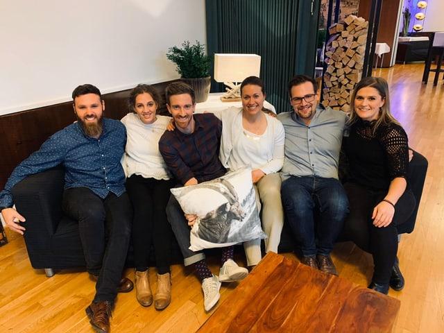 Sechs Personen sitzen auf einem Sofa