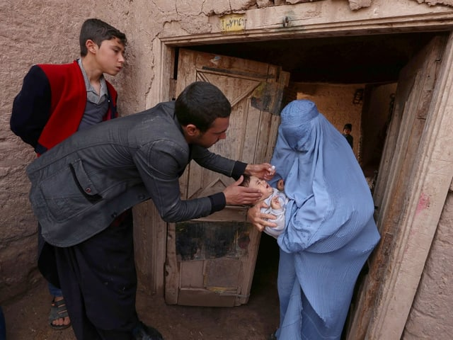 Ein Mann impft das Baby einer verschleierten Frau vor deren Haustür.