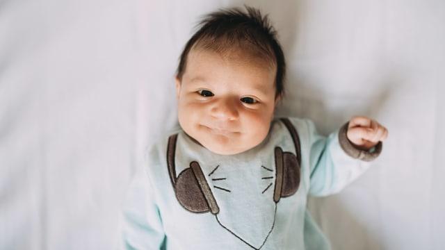 Symbolbild: Baby im Strampelanzug, es lächelt.